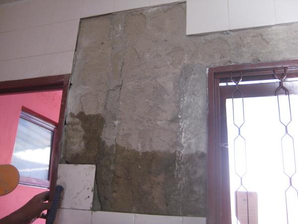 parede umedecida com um pano e aplicando o azulejo novo
