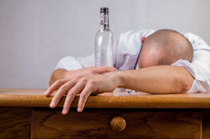 homem bebado debruçado sobre a mesa com uma garrafa ao lado