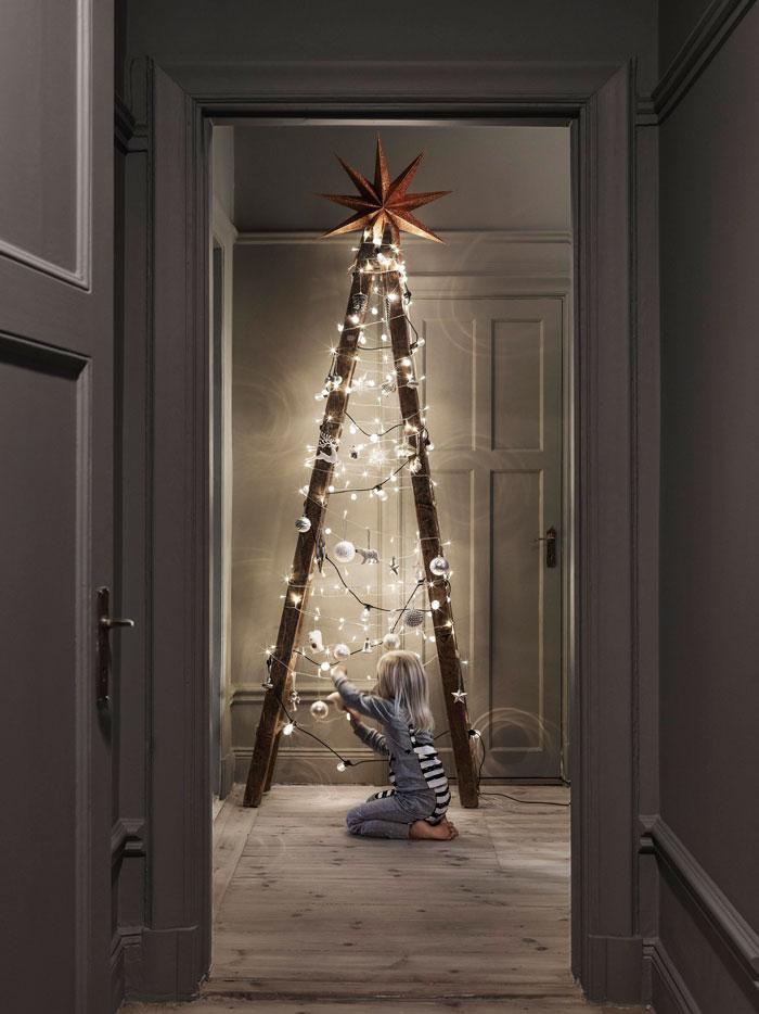 criança montando luzes numa arvore de escada