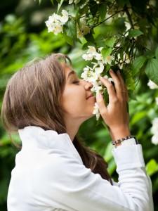 mulher cheirando flores de jasmim