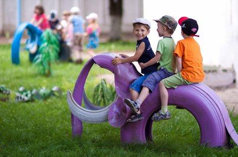 crianças brincando num pneu com forma de elefante