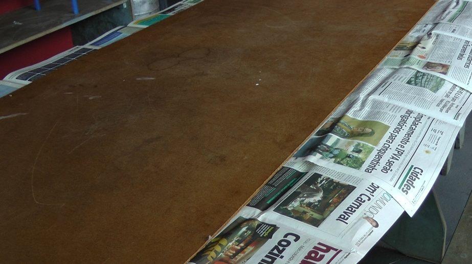 madeira compensado em cima de mesa forrada com jornal