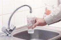 homem pegando um copo de agua na torneira