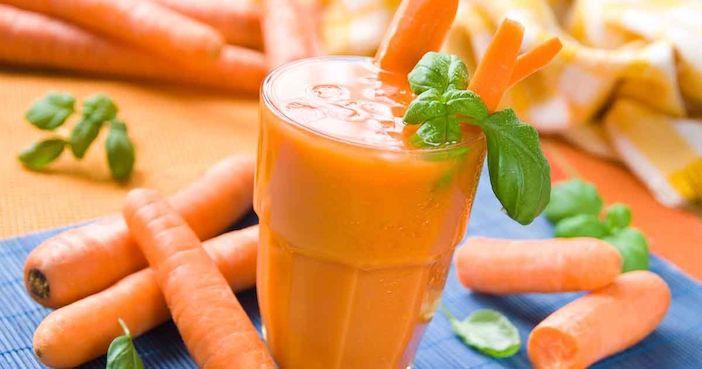 varias cenouras e um copo cheio de suco de cenoura