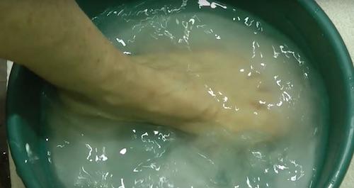 pés mergulhados numa bacia de água com bicarbonato