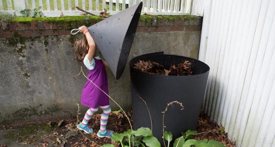 criança levanta a tampa de uma composteira