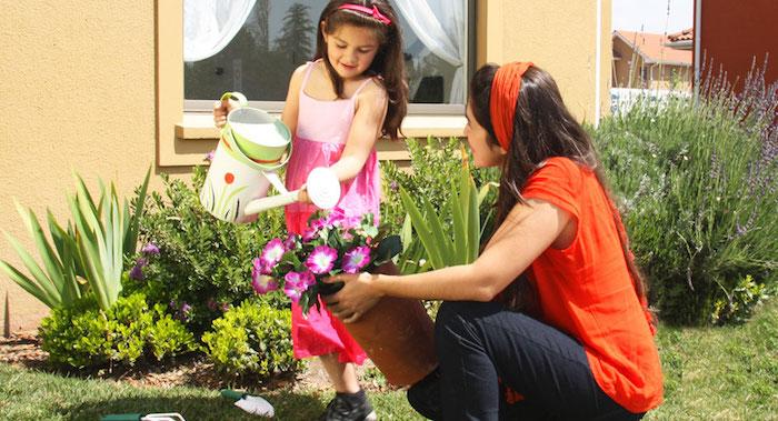 mae e filha regando flores no jardim