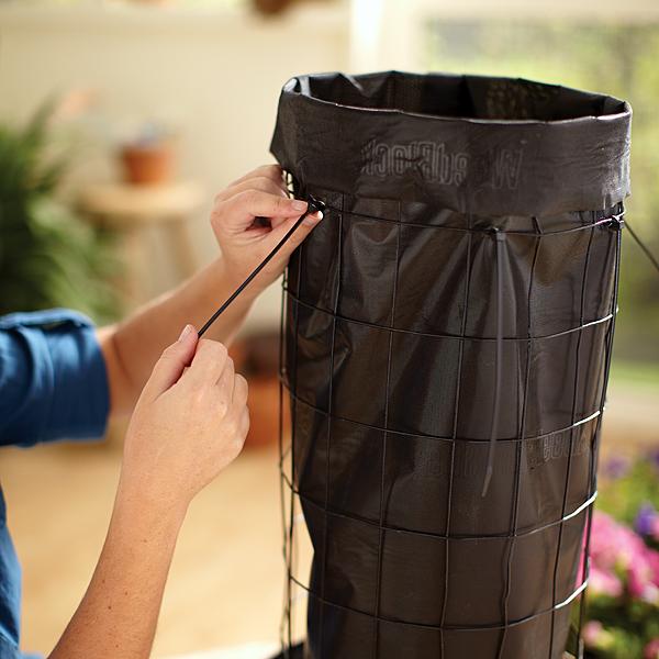 mulher prende manta de jardim no cilindro de arame com abraçadeira de plástico