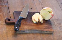 tábua de cortar com uma maçã em pedaços e uma faca