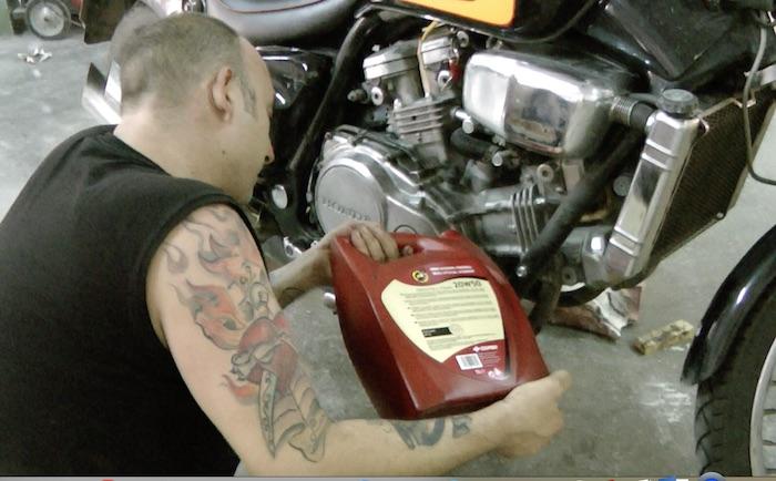 homem completando óleo moto