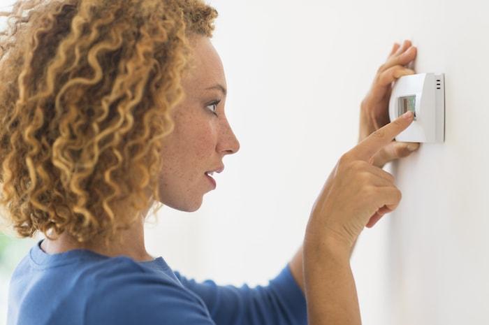mulher tocando termostato