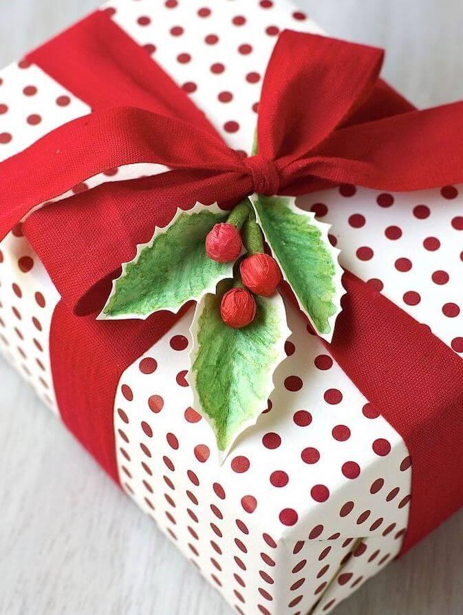 presente decorado com fita vermelha e folhas de papel